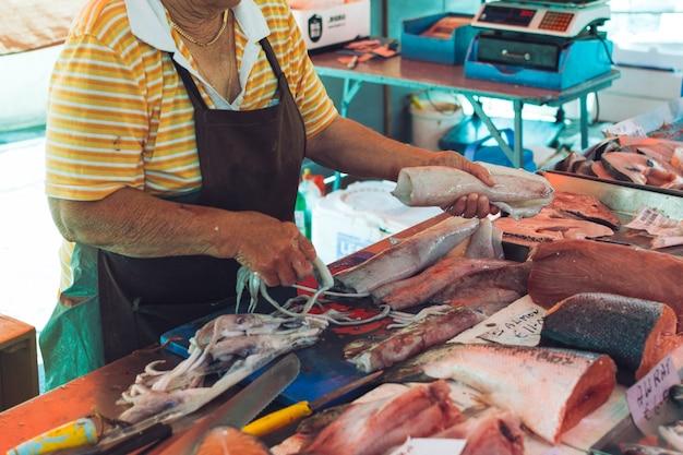Резка кальмаров на рыбном рынке