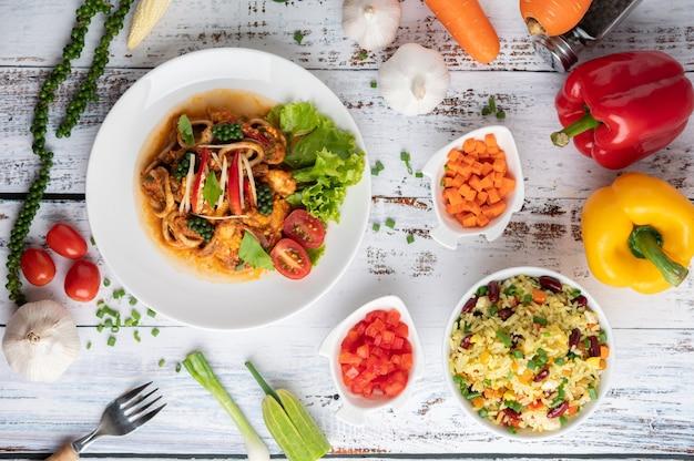 Кальмары обжаренные с пастой карри на белой тарелке с овощами и гарнирами на белом деревянном полу.