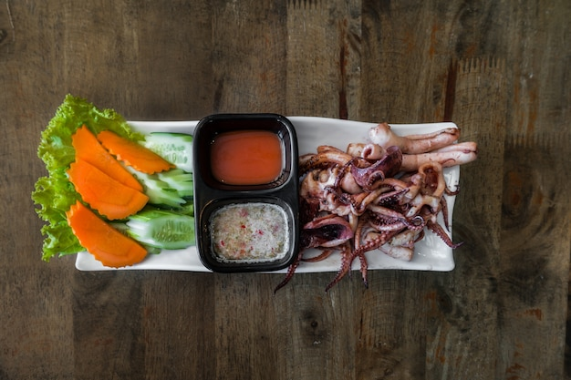 Squid grilled  on white dish with chili sauce on wood table background
