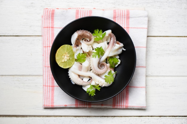 Squid salad bowl with lemon herbs and spices on wooden surface
