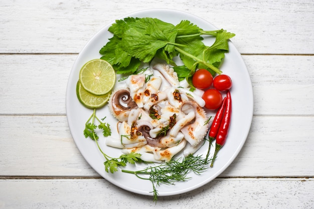 Squid salad with lemon herbs and spices on wooden background top view tentacles octopus cooked appetizer food hot and spicy chilli sauce seafood cooked served on white plate in the restaurant