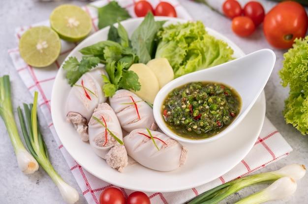 Кальмары, фаршированные вареной свининой с соусом из морепродуктов.