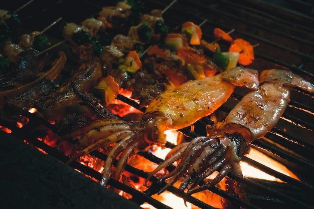 오징어, 야채, 버섯, 개구리, 거리에서 모닥불에 요리. 길거리 베트남 음식. 전통적인 아시아 음식입니다.