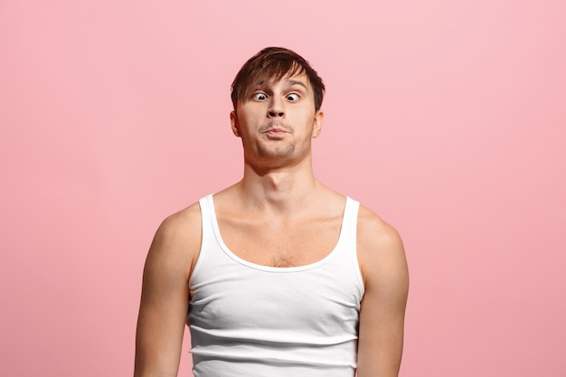 The squint eyed man with weird expression isolated on pink wall
