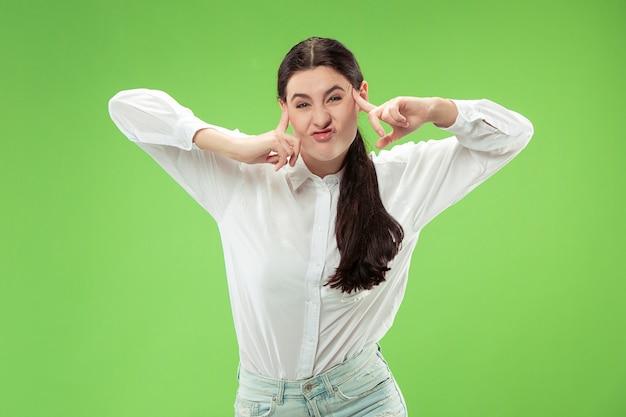 変な表情の斜視女性。緑のスタジオの背景に分離された美しい女性の半分の長さの肖像画。