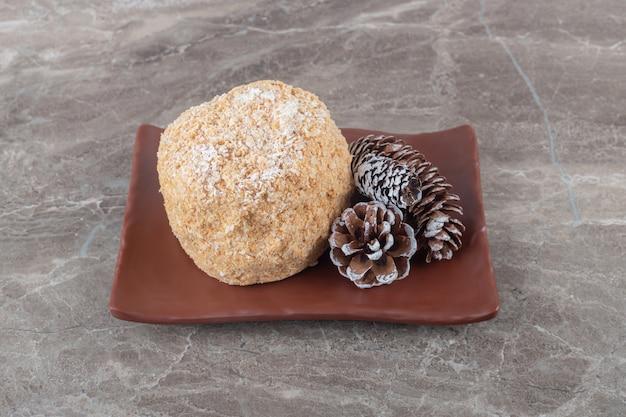 大理石の表面の茶色の大皿にリスのケーキと松の円錐形