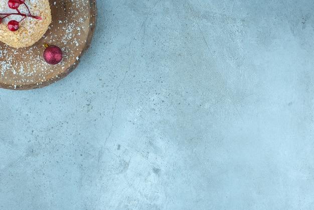 Torta di scoiattolo decorata con ornamenti natalizi su tavola in marmo.