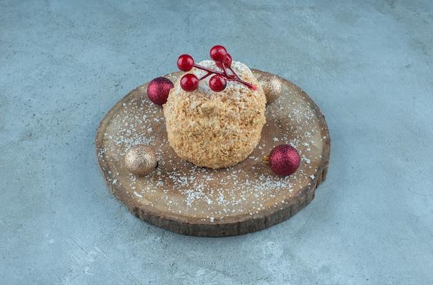 Торт с белкой, украшенный елочными украшениями на доске на мраморе.