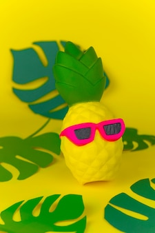 Squishy toy pineapple in sunglasses on yellow background among paper cut tropical leaves