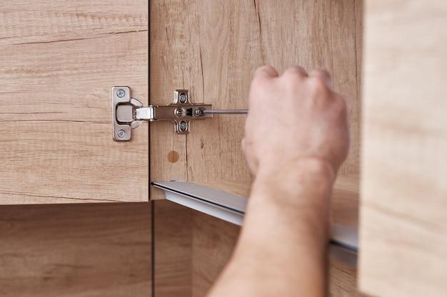 Отвертка, фиксирующая дверь кухонного шкафа крупным планом