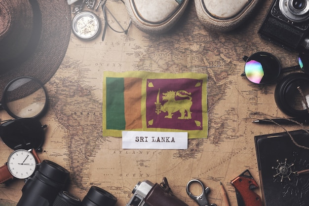 Sri lanka flag between traveler's accessories on old vintage map. overhead shot