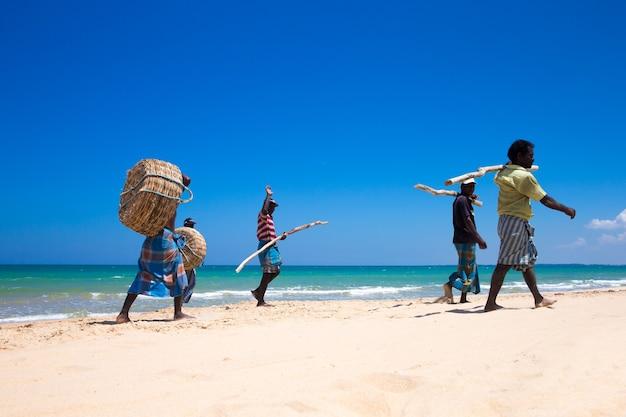 スリランカ-マッハ23:地元の漁師が2017年マッハ23にスリランカのコスゴダで、インド洋から漁網を引っ張っています。スリランカでの釣りは彼らが生計を立てる方法です。