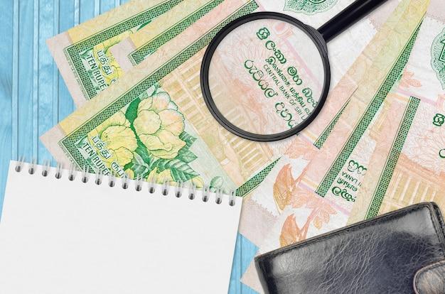 Банкноты шри-ланки рупии и увеличительное стекло с черным кошельком и блокнотом