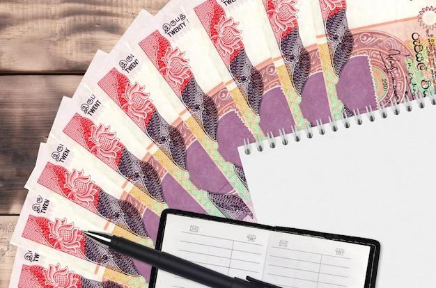 스리랑카 루피 지폐 팬과 연락처 책과 검은 색 펜 메모장