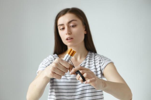 담배와 가위를 다발로 들고 줄무늬 티셔츠를 입은 끔찍한 젊은 검은 머리 여성은 담배를 끊고 나쁜 습관을 영원히 포기하기로 결정하면서 반으로 자릅니다. 선택적 초점