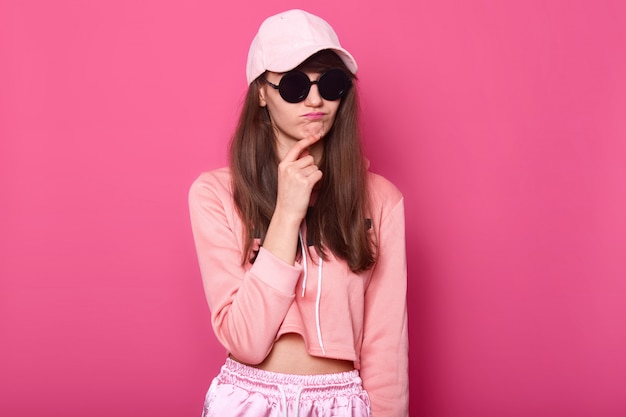 Srusio shot of stylish teenager girl wearing fashionable shortened pink hoodie, cap and black subglasses, touches her chin with thoun ghtful facialexpression. female. people concept.