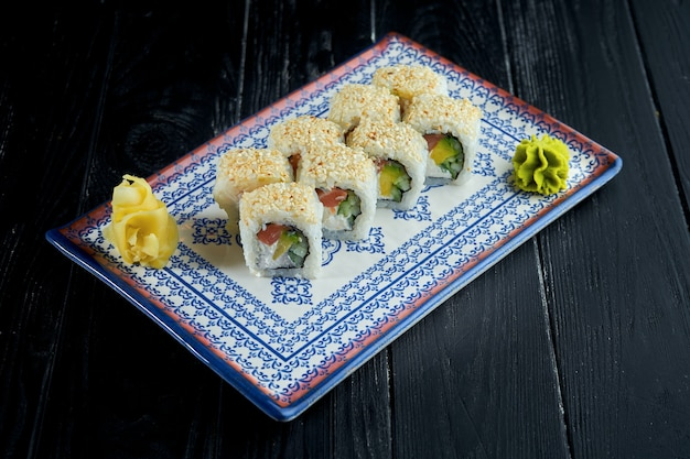 Ssushi roll in sesame seeds with salmon, avocado and cream cheese in a blue plate.
