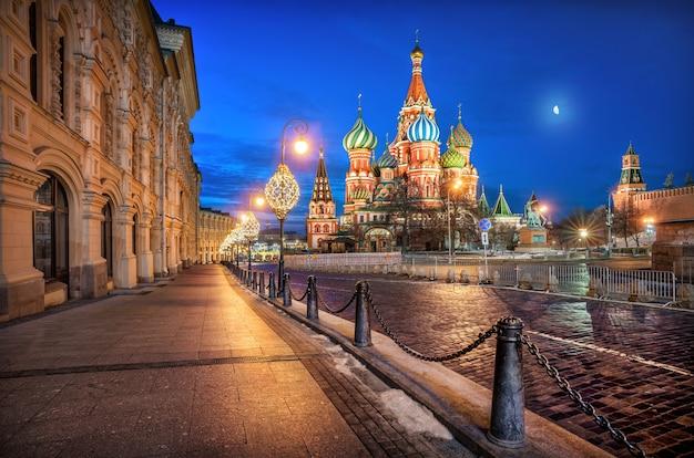 Собор василия блаженного под голубым небом на красной площади в москве при лунном свете и фонарях зимним утром