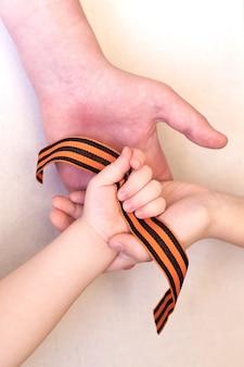 Георгиевская лента в трех детских руках, день защитника отечества, день победы.