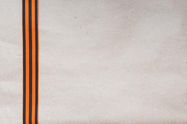 Георгиевская ленточка на фоне старой бумаги.