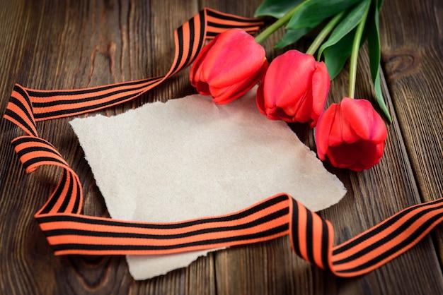 セントジョージのリボン、赤いチューリップ、木製の背景に紙のグリーティングカード。勝利の日または祖国の擁護者の日。