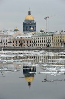 St. isaac's cathedral and the construction crane is reflected in the neva river in the spring, st. petersburg, russia