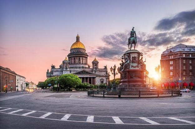 Исаакиевский собор под голубым небом и розовый памятник николаю первому на исаакиевской площади ранним утром в санкт-петербурге.