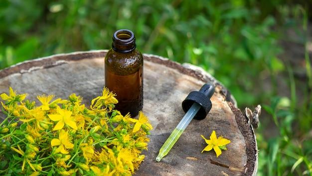 ガラス瓶に入ったセントジョンズワートフラワーオイル。木製の背景に。セレクティブフォーカス