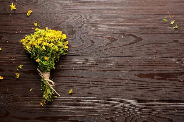 Зверобой, растение с желтыми цветами, лечебная трава на деревянном столе, вид сверху.