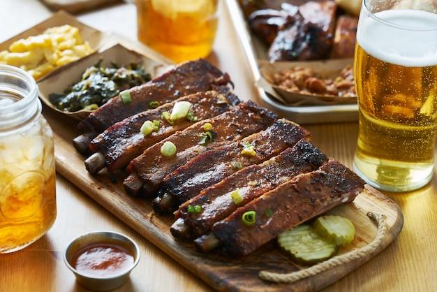 テーブルトップのセントルイススタイルのバーベキューリブ、スイートティー、ビール、コラードグリーン、マック&チーズ