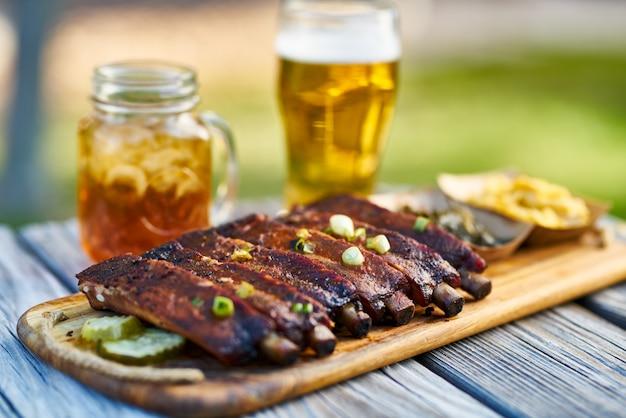日当たりの良い夏の日の間にピクニックテーブルの上のコラードグリーンとマック&チーズの外でセントルイススタイルのバーベキューリブ