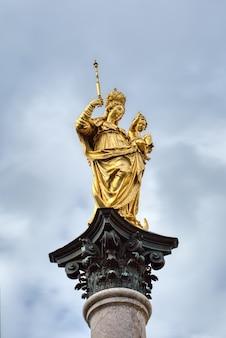 Колонна святой марии, mariensaeule на площади мариенплац на фоне серого облачного неба, мюнхен, бавария, германия