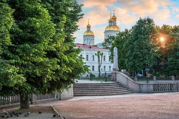 Свято-николаевский собор на крюковом канале в санкт-петербурге ранним летним утром и много голубей под деревом