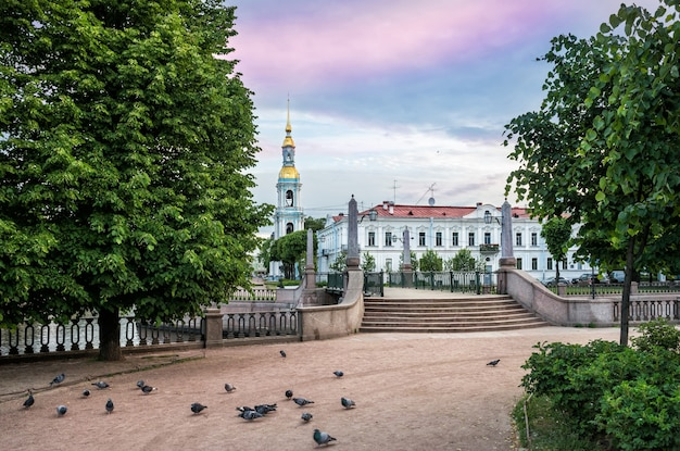Свято-николаевский собор с колокольней на крюковом канале в санкт-петербурге и голубями у ступенек ранним солнечным утром.