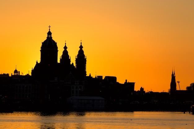 Горизонт городского пейзажа амстердама с церковью st nicholas sint-nicolaaskerk во время захода солнца. живописный амстердам, нидерланды.