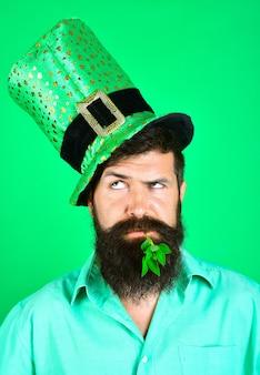 성 패트릭의 날. 레프 러콘 요정 모자에 수염 된 남자입니다. 입에 클로버. 수염 난 레프 러콘. 수염 난 남자.
