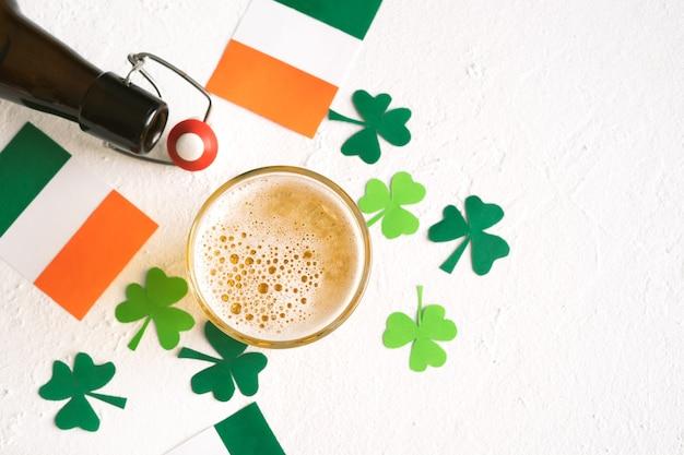 성 패트릭의 날 축하. 아일랜드 국기와 토끼풀로 장식 된 맥주. 공간을 복사하십시오. 평면도.