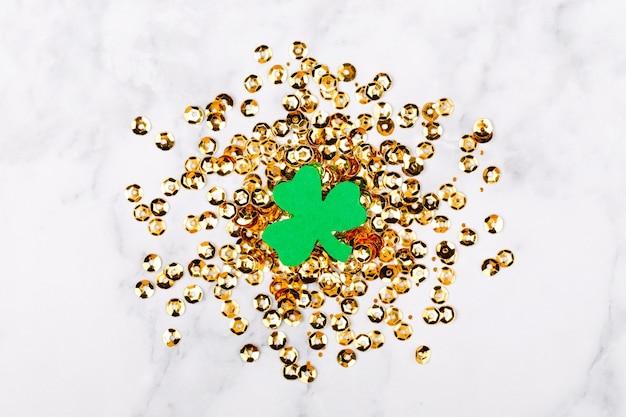 Концепция дня святого патрика. фон с листьями клевера и золотым конфетти. шаблон макета. вид сверху