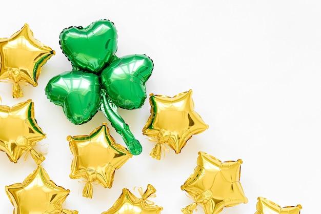 Украшение дня святого патрика. воздушные шары из золотой фольги в форме звезд и зеленые шары в форме листа клевера. концепция праздника и торжества. металлические воздушные шары.