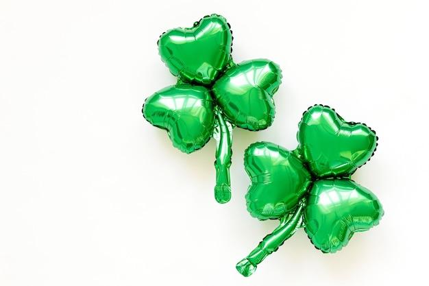 Украшение дня святого патрика. зеленые шары формы листьев клевера. концепция праздника и торжества. металлические воздушные шары.