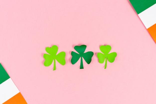 성 패트릭의 날. 세 클로버 크림 배경에 아일랜드 플래그와 함께 나뭇잎. 공간을 복사하십시오. 평면도.