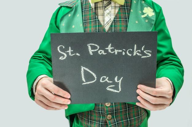 Отрежьте взгляд человека в зеленом костюме держа темную таблетку с днем st. patrick письменных слов. изолированные на сером.