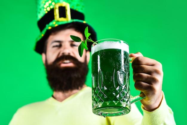 День святого патрика крупным планом портрет счастливого бородатого мужчины в шляпе лепрекона с клевером в стакане пива