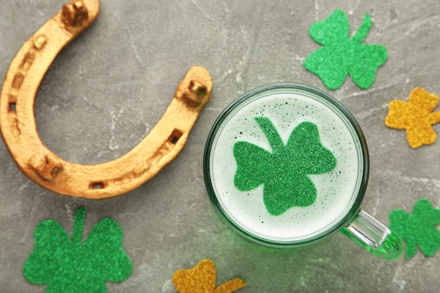 St. patricks day. clover in beer mug on grey wall with space for copy, text, your words. top view