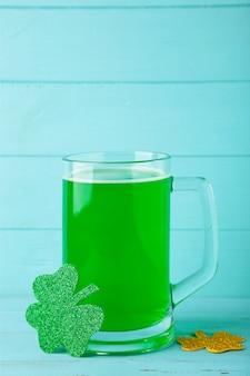 聖パトリックの日、青い背景にビールと緑のシャムロック。上面図