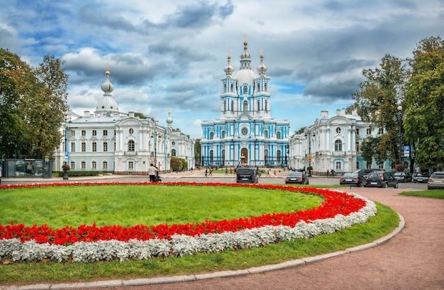 Санкт-петербург. смольный собор и клумба с красными цветами перед ним в осенний день