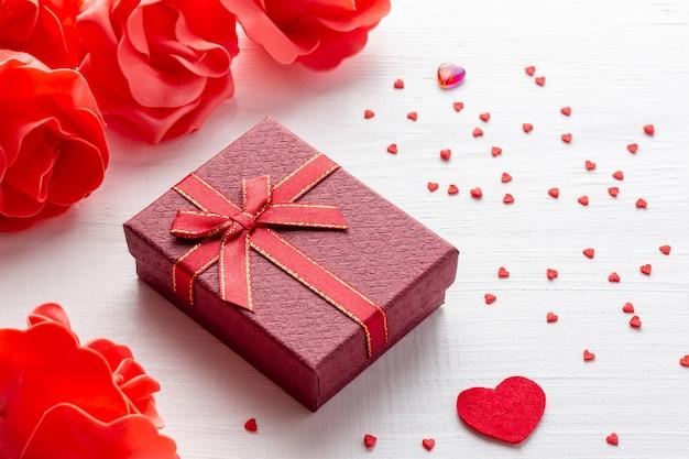 赤いギフトボックスと白い木の背景に花とハートの聖バレンタインデーのアレンジメント