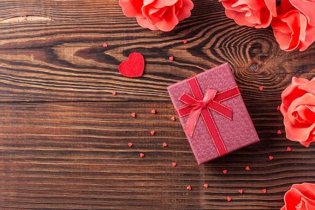 Композиция дня святого валентина с фиолетовой подарочной коробкой и красными сердцами на деревянном фоне