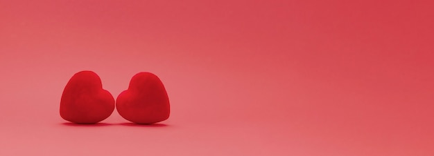St.valentine day concept. two red velvet hearts on a gradient red background . copy space. banner size. Premium Photo