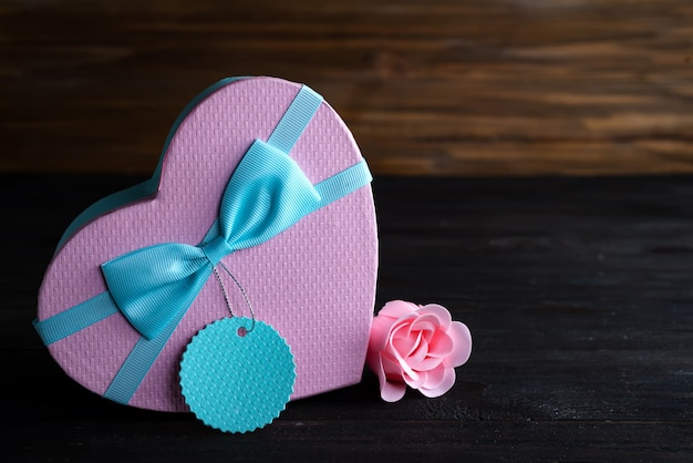 St valentine's day box heart and pink rose on dark wooden background, copy space